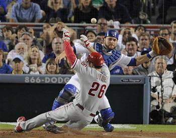 Philadelphia's Chase Utley slides home safely as Los Angeles Dodgers catcher Russell Martin can't make the catch on a wild throw from shortstop Rafael Furcal on Wednesday.