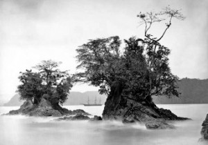View of Three-Masted Sailing Ship Between Tree-Covered Rock Formations in Misty Harbor, 1870 sm